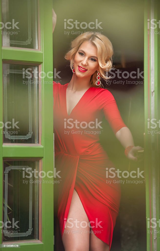Charming young blonde with red dress posing in door frame stock photo