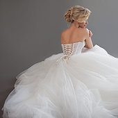 Charming young bride in luxurious wedding dress. Pretty girl in