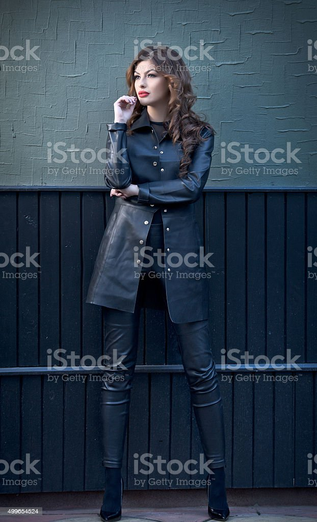Charming young brunette woman in black leather outfit stock photo