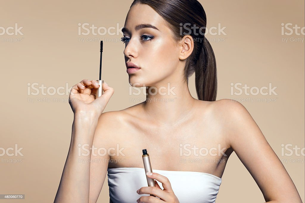 Charming young girl applying mascara stock photo