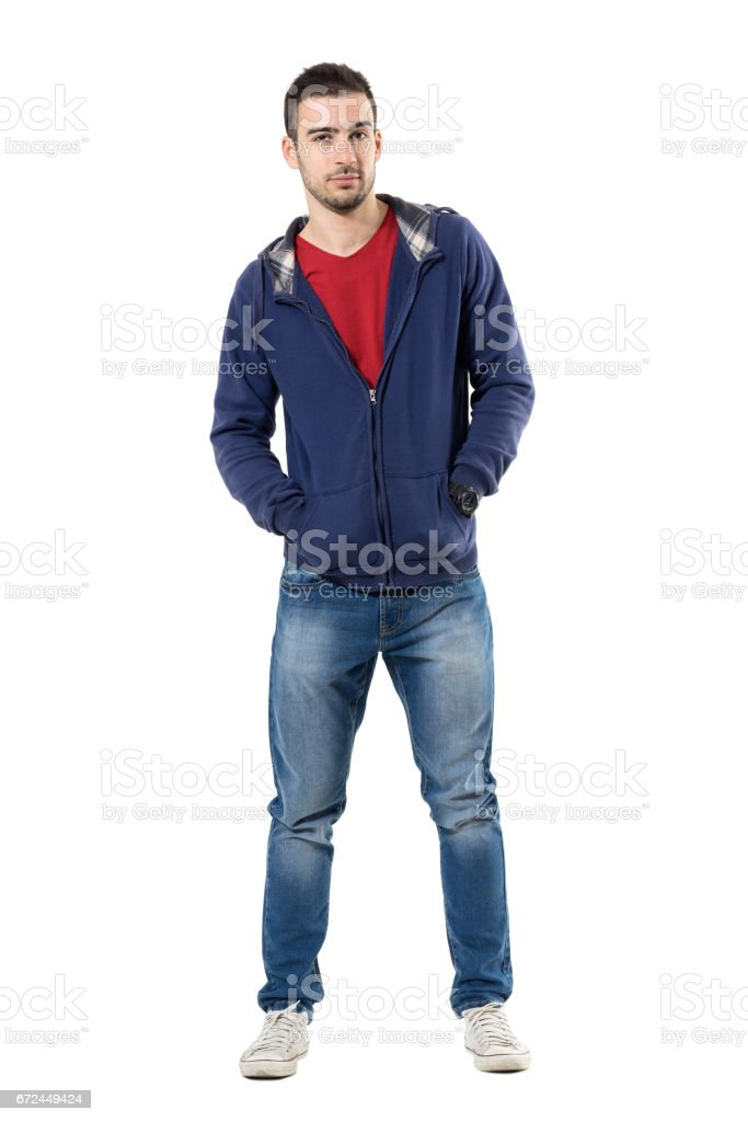 Charming young guy in blue sweatshirt with hands in pockets looking at camera. stock photo