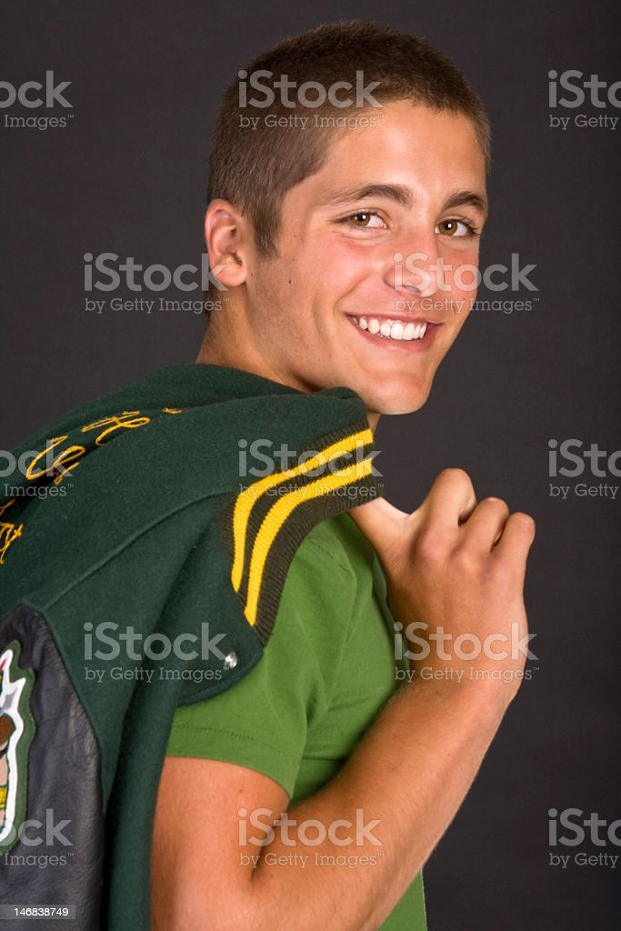 A charming young man happily carrying a letterman jacket stock photo