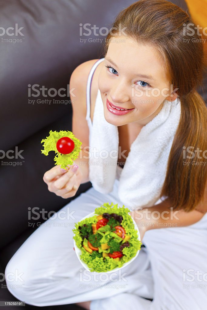 Charming young woman eating green vegetable salad royalty-free stock photo