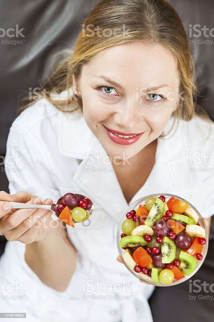 Charming young woman offering teaspoon full of sliced ​​fruits, smiling royalty-free stock photo