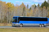 Charted bus on  highway. Fall colors in the background.