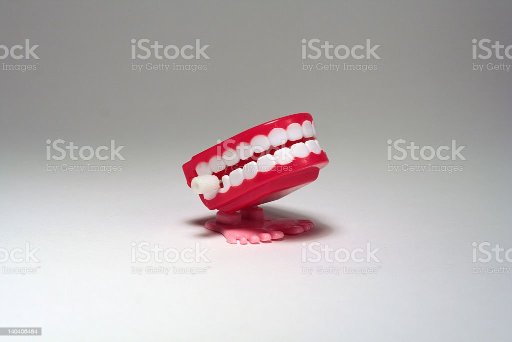 Chattering tea toy with small pink feet on white surface stock photo