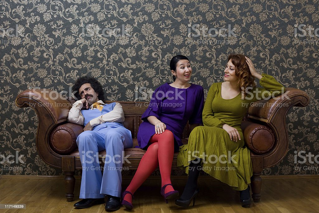 Chatting gossip housewifes and looser sullen men in 1970s style royalty-free stock photo