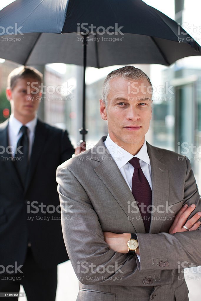 Chauffeur holding umbrella for businessman stock photo