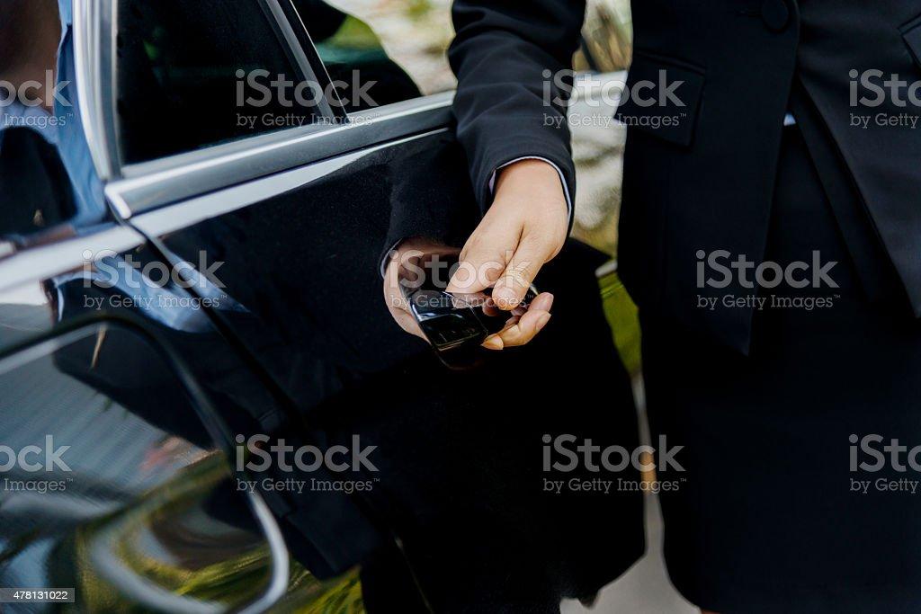Chauffeur open car door stock photo