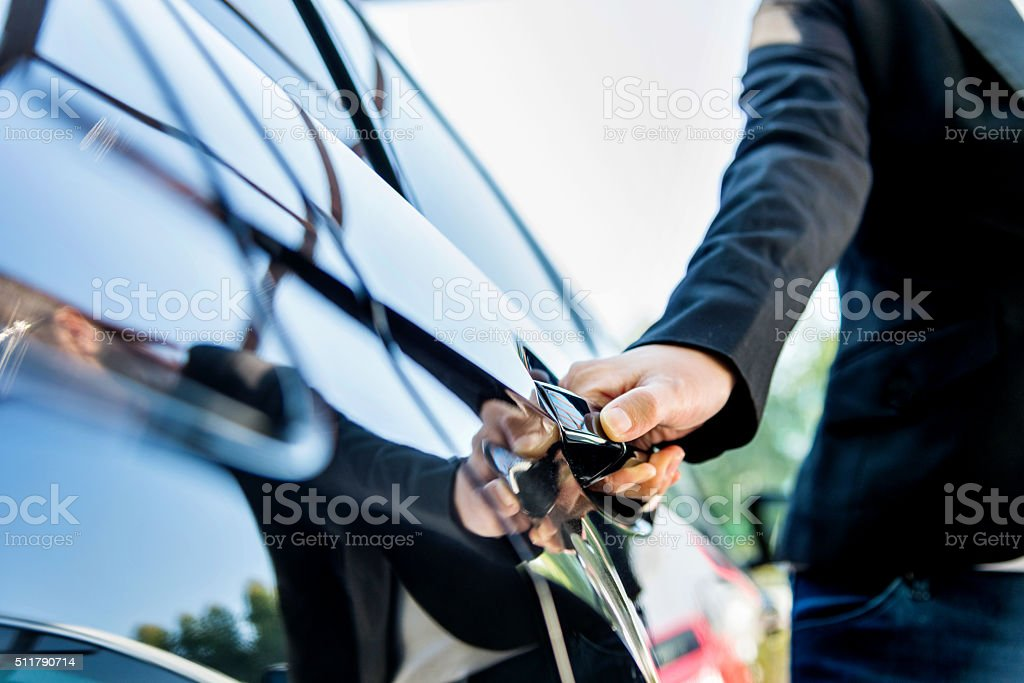 Chauffeur open car door stock photo