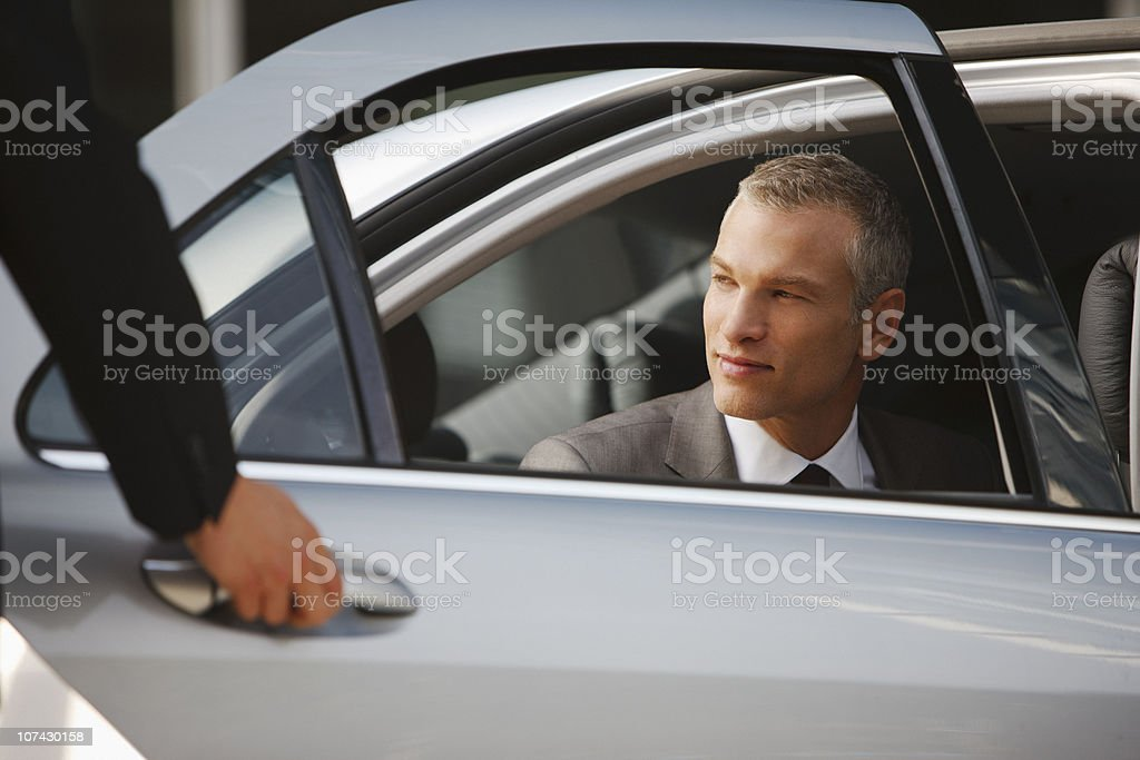 Chauffeur opening car door for businessman stock photo