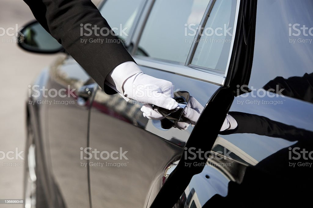 Chauffeur opening / closing luxury car door stock photo