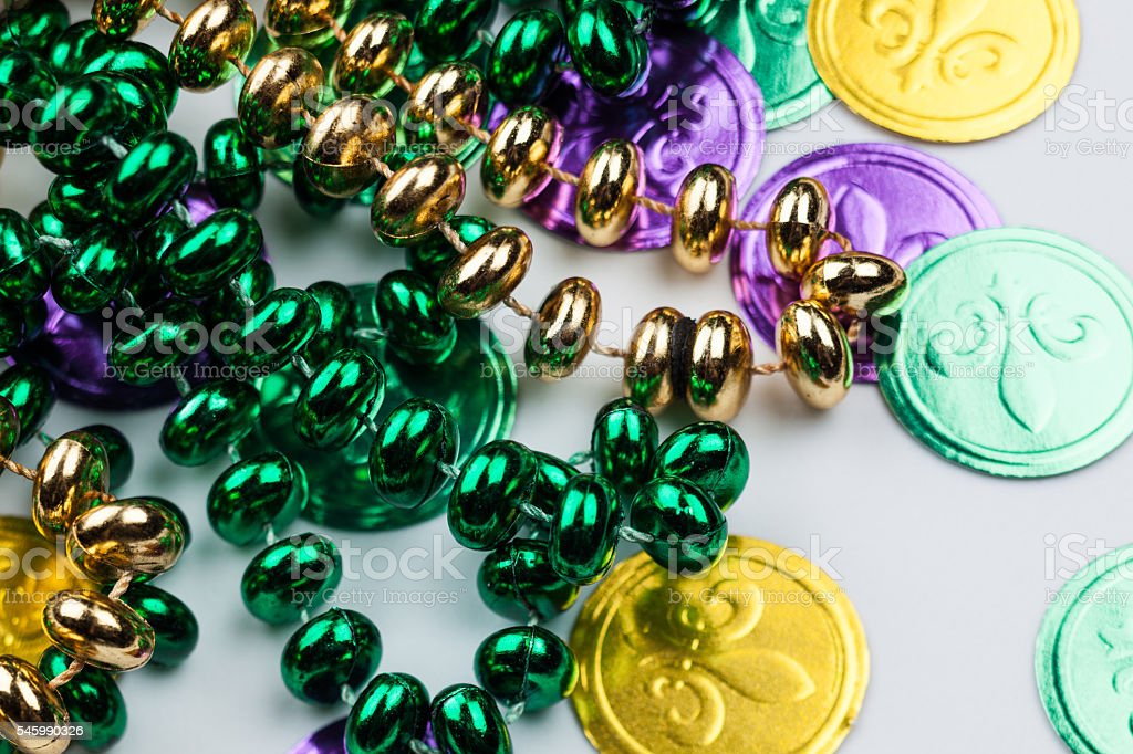 Cheap plastic Mardi Gras coins and beads on table stock photo
