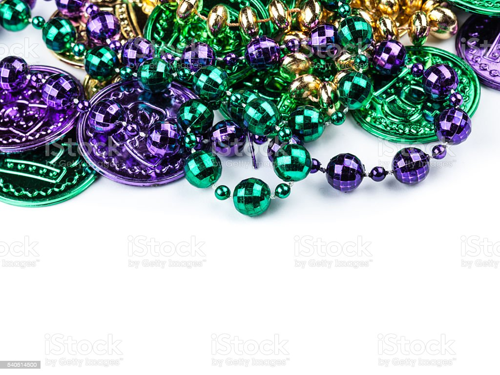 Cheap plastic Mardi Gras coins and beads with copyspace stock photo