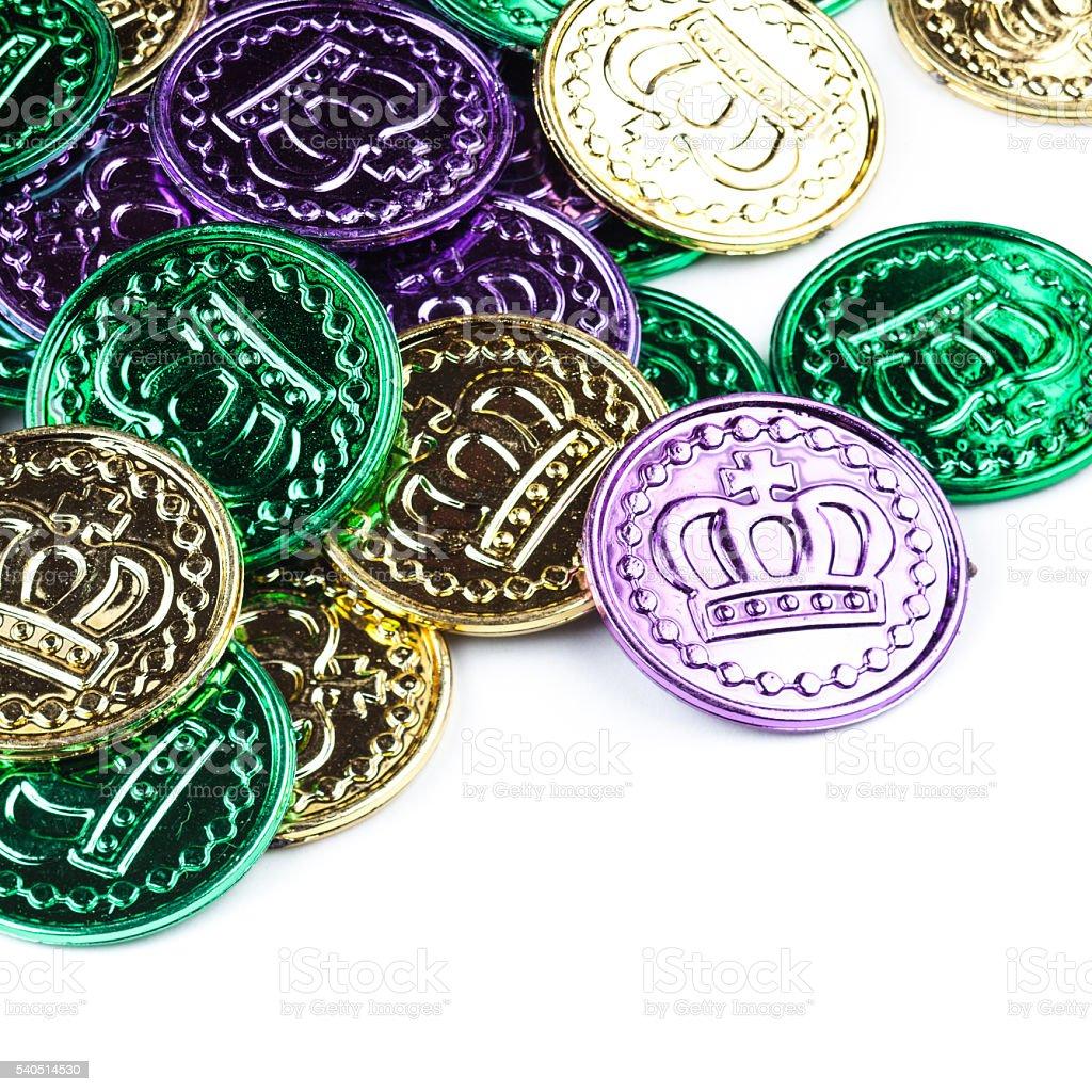 Cheap plastic Mardi Gras coins on white stock photo