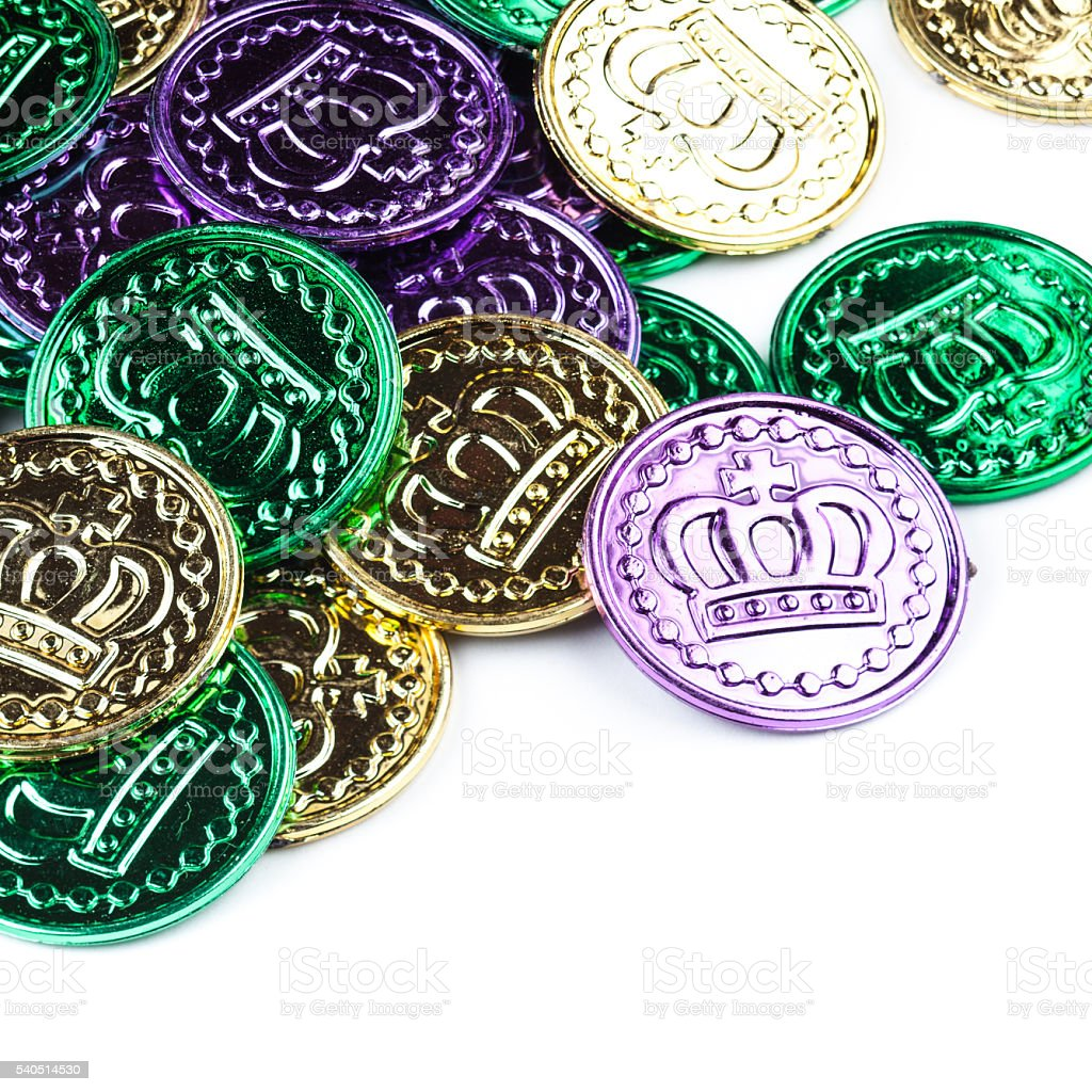 Cheap plastic Mardi Gras coins on white stock photo