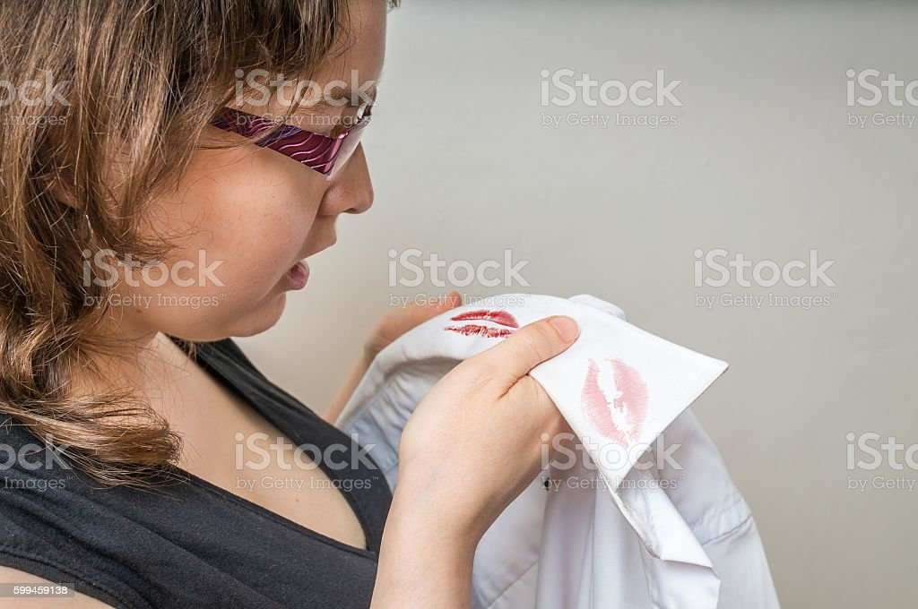 Cheating and infidelity. Jealousy woman found lipstick stains on shirt. stock photo