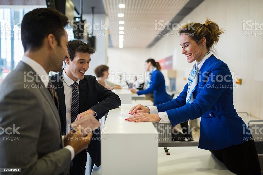 Check in counter stewardess and business traveler. stock photo