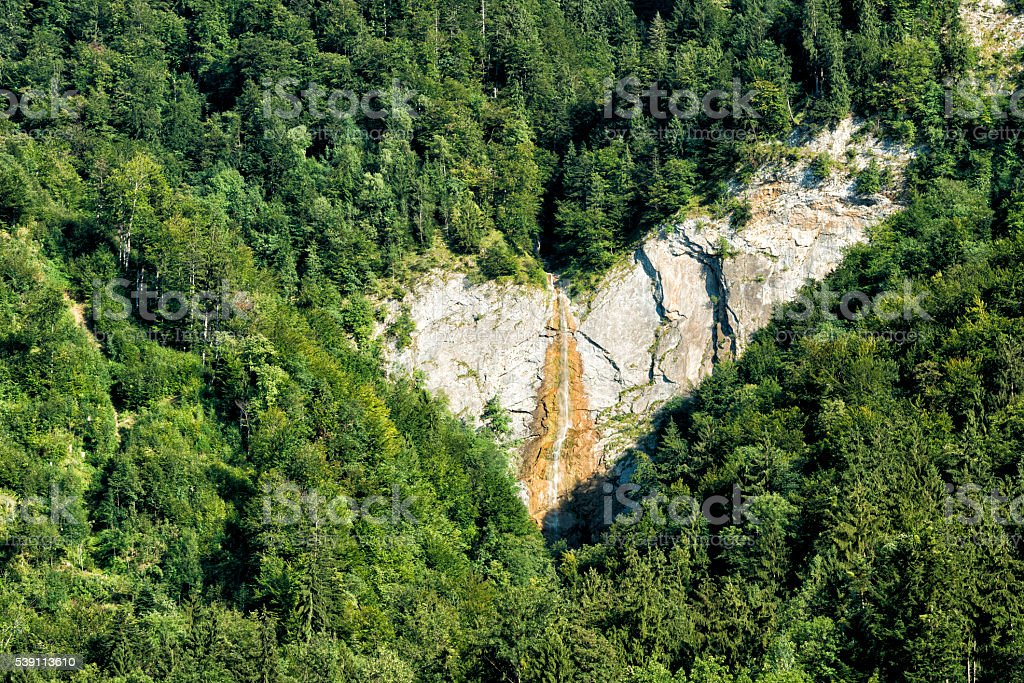 check mark on rock with waterfall in forest stock photo