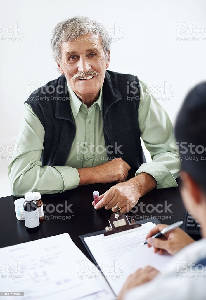 Check up - Happy senior man sitting with a doctor royalty-free stock photo