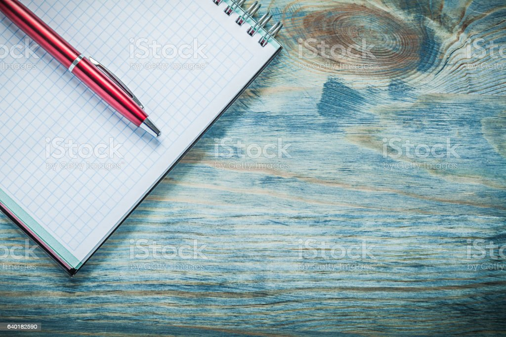 Checked blank notepad ball-point pen on wood board education stock photo