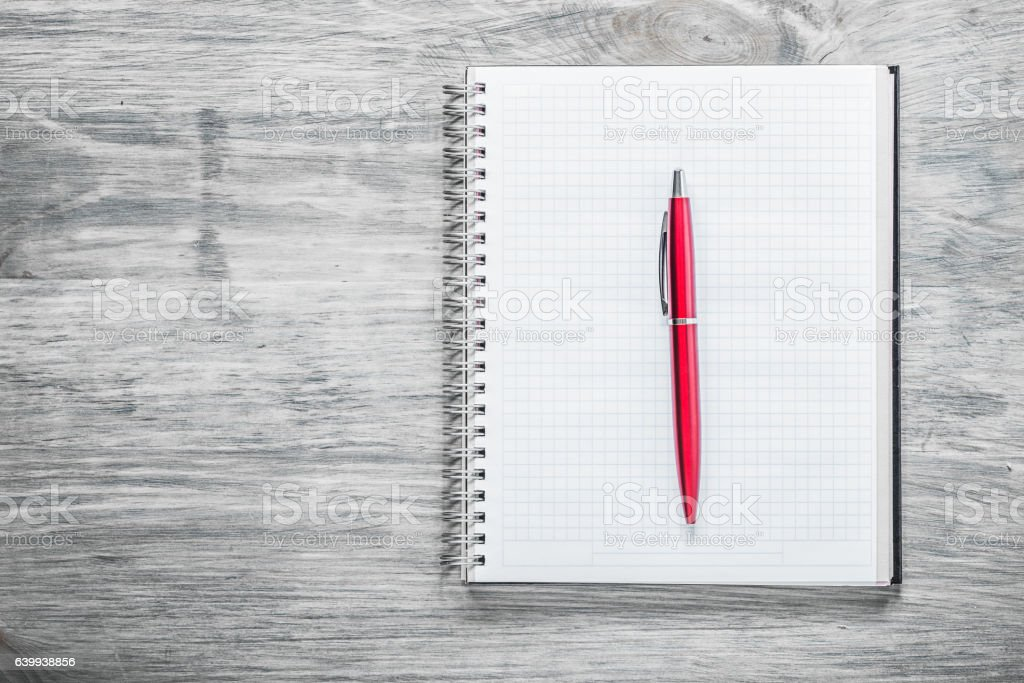 Checked notepad pen on wooden board education concept stock photo