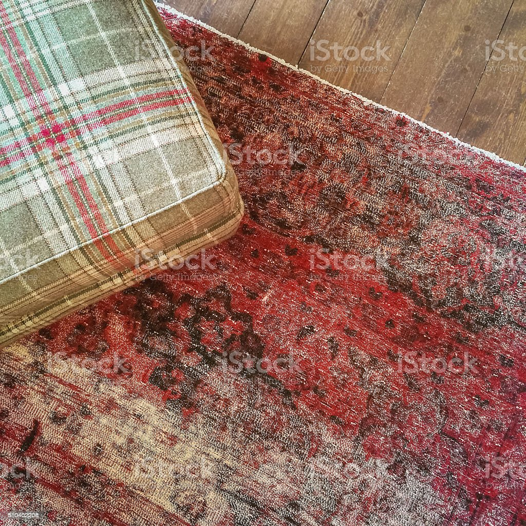 Checked textile hassock and vintage style carpet stock photo