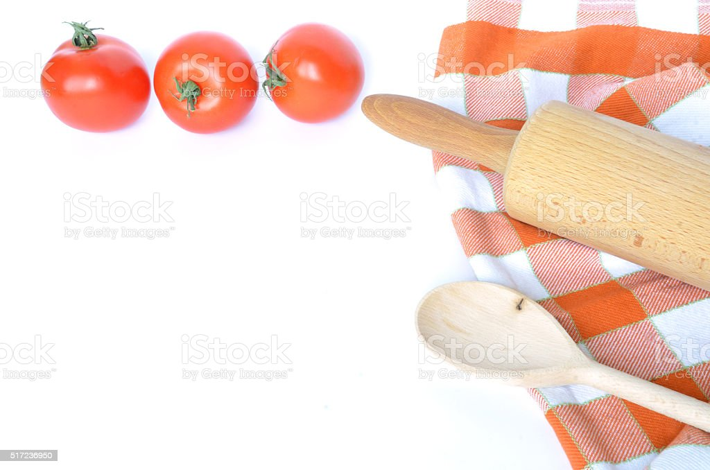 Checkered dishcloth, spoon, tomatoes and rolling pin isolated on white stock photo