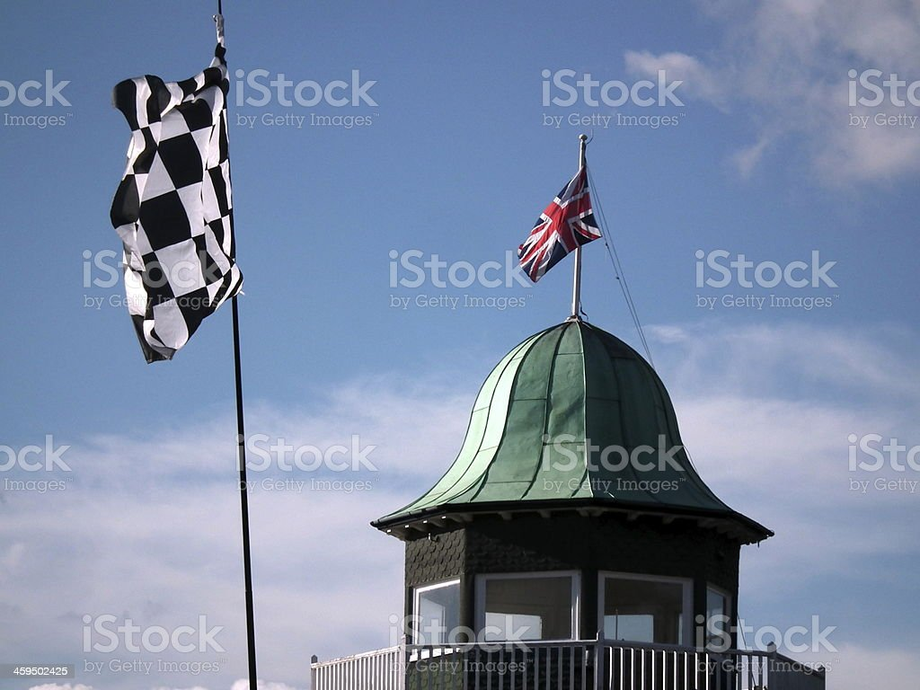 A checkered flag flutters in the wind with a United Kingdom Union...