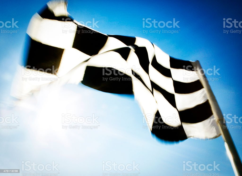 Checkered flag blowing in the wind. stock photo