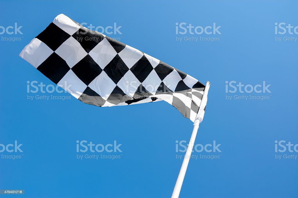 Checkered flag flying on blue sky background stock photo