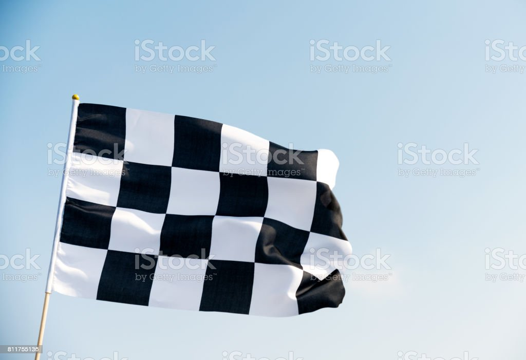 Checkered flag flying on blue sky stock photo