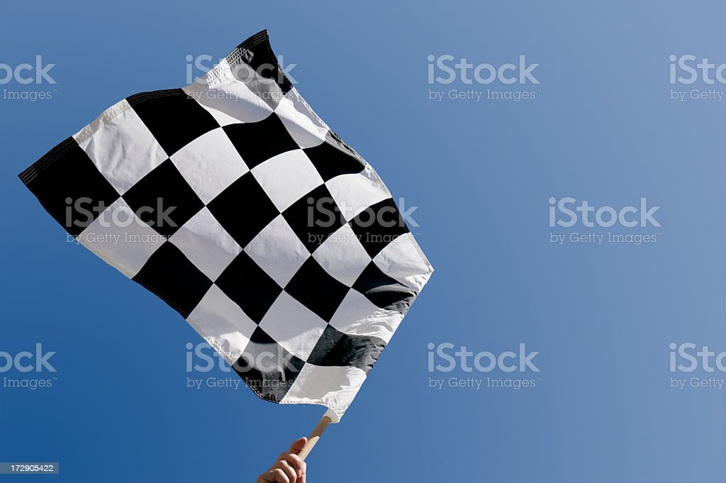 Checkered flag waving against blue sky stock photo