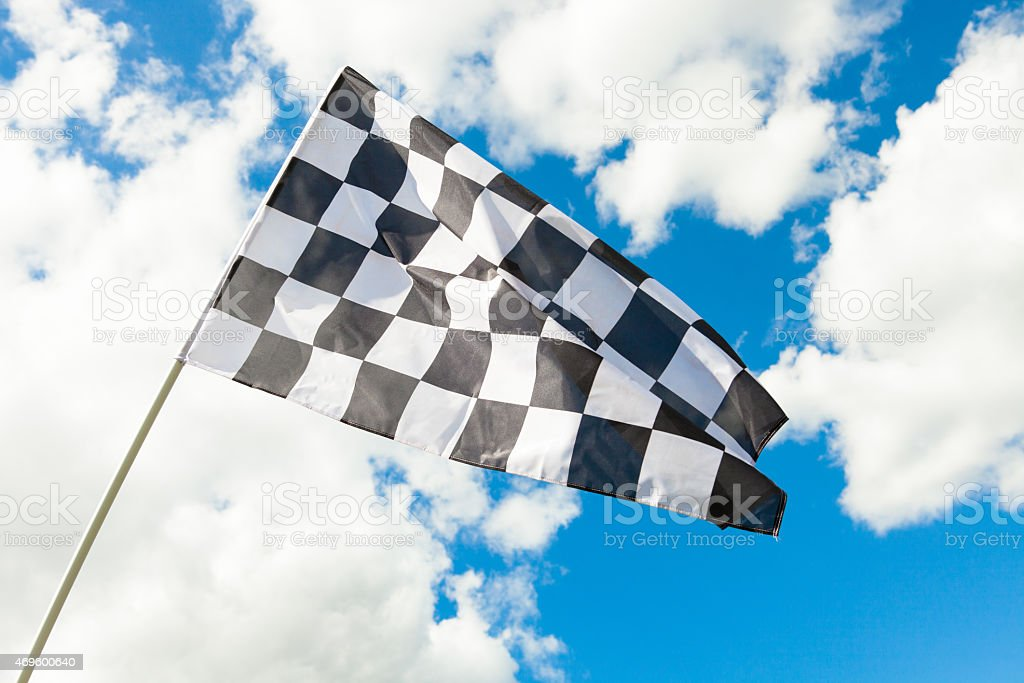 Checkered flag waving in the wind - clouds on background stock photo