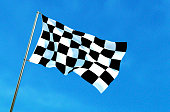 Checkered flag waving on the blue sky background.
