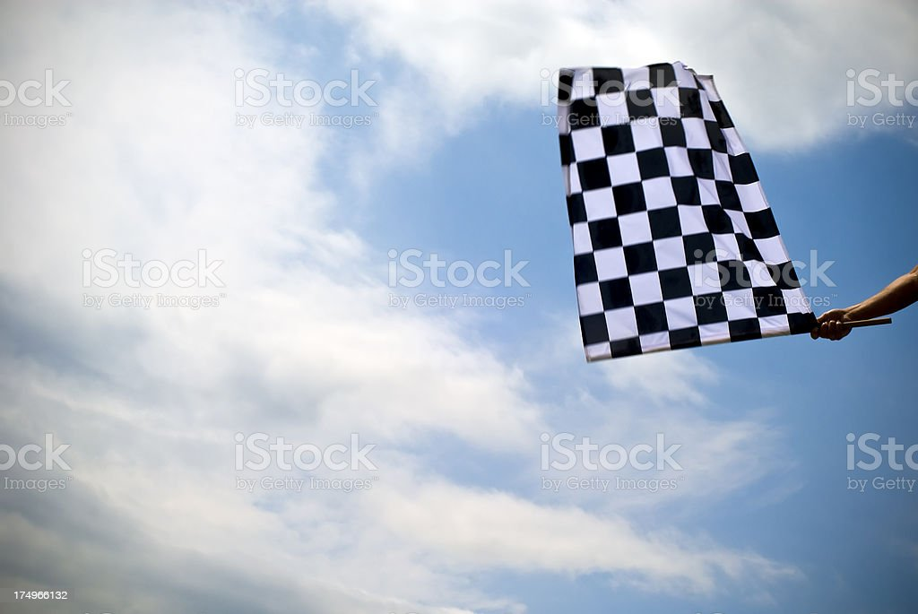 Checkered flag waving under a blue sky stock photo
