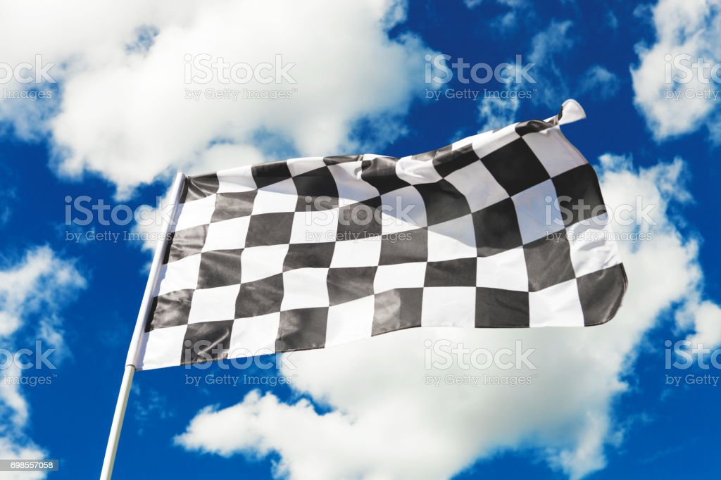 Checkered flag waving with blue sky and clouds behind it. Filtered image: cross processed vintage effect. stock photo