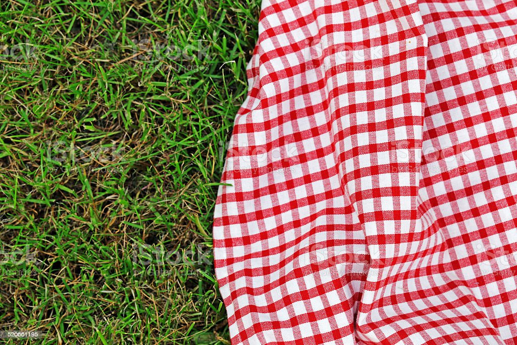 checkered plaid for picnic on green grass stock photo