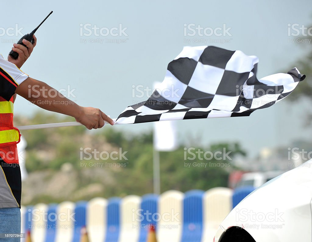 Checkered racing flag being shown to start the race stock photo