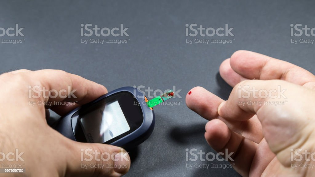 checking blood glucose for treatment studio image stock photo