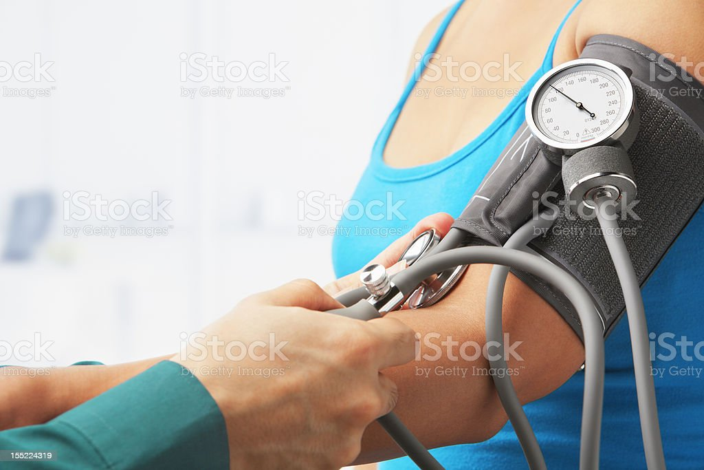 Checking blood pressure of female patient stock photo