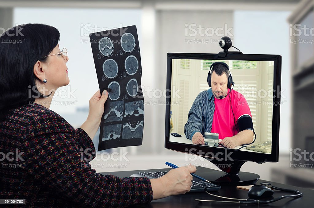 Checking brain x-ray results with online patient stock photo