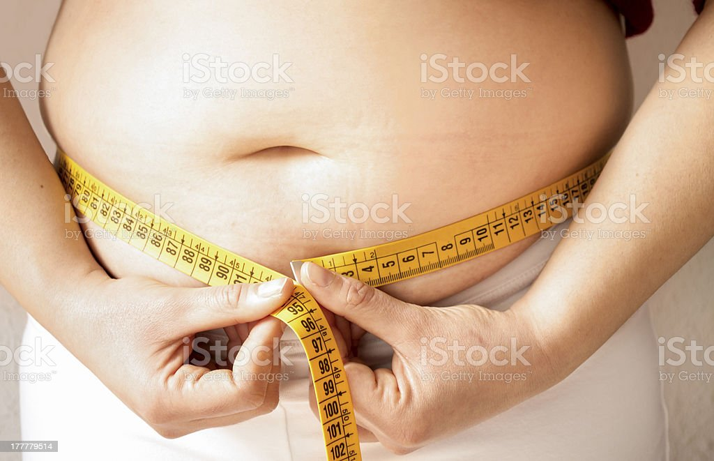 checking fats on her body with a meter stock photo
