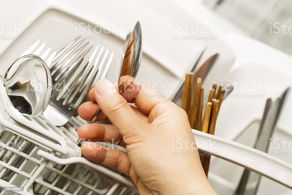 Checking for Cleanliness of Silverware from Dishwasher royalty-free stock photo