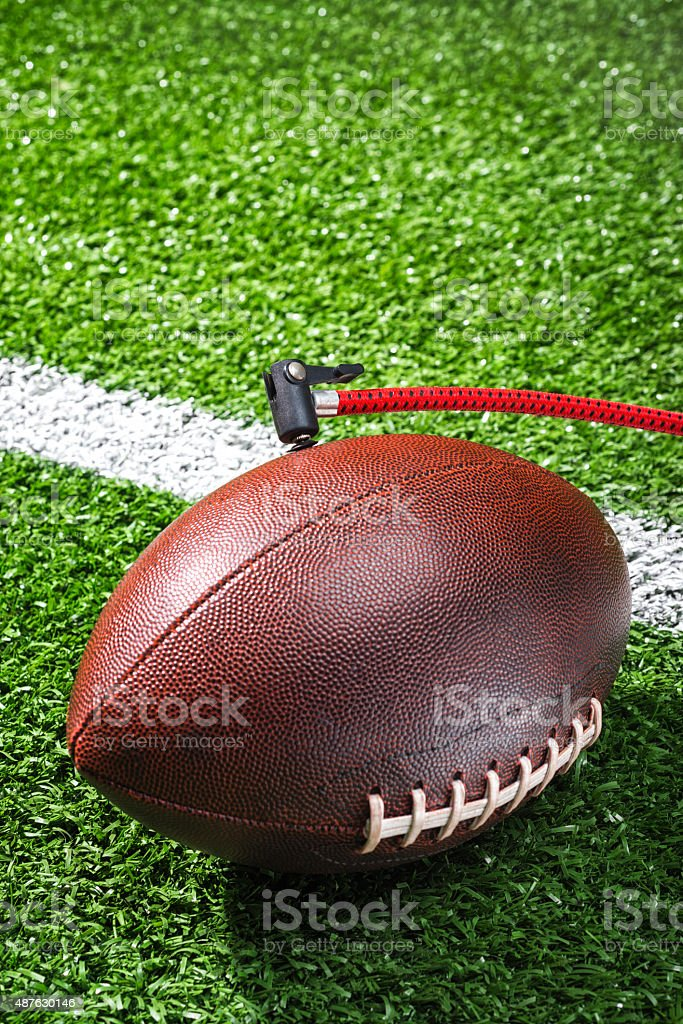Checking for proper air pressure in an American Football stock photo