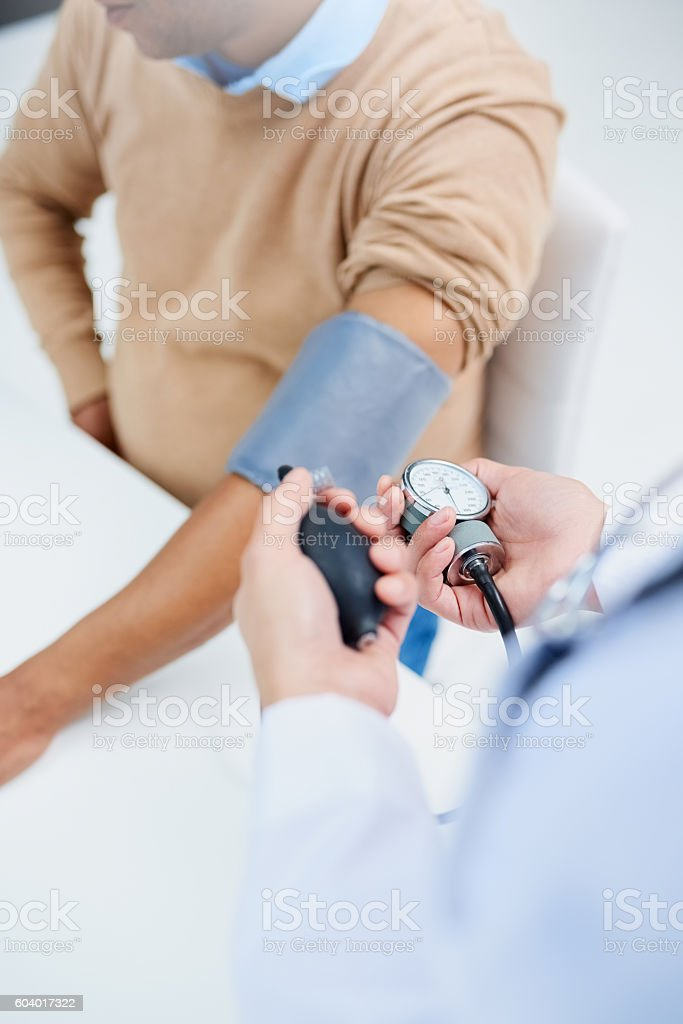 Checking his blood pressure stock photo