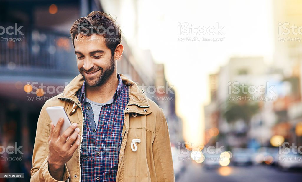 Checking his texts while in the city stock photo