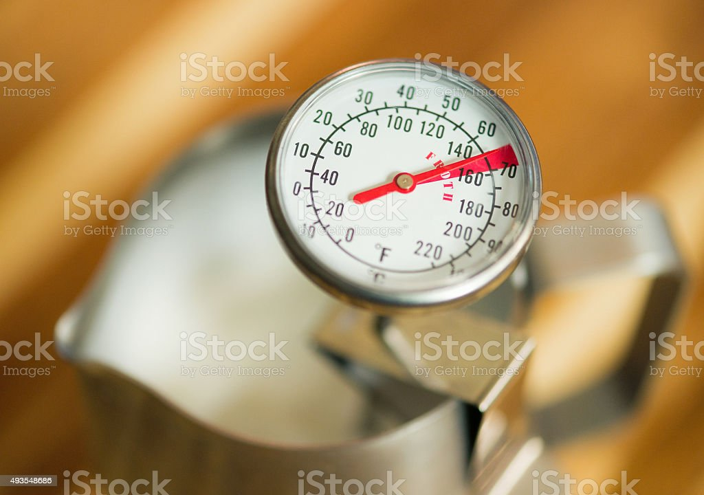Checking milk temperature for making coffee stock photo