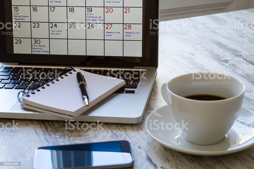 Checking monthly activities in the calendar in the laptop stock photo