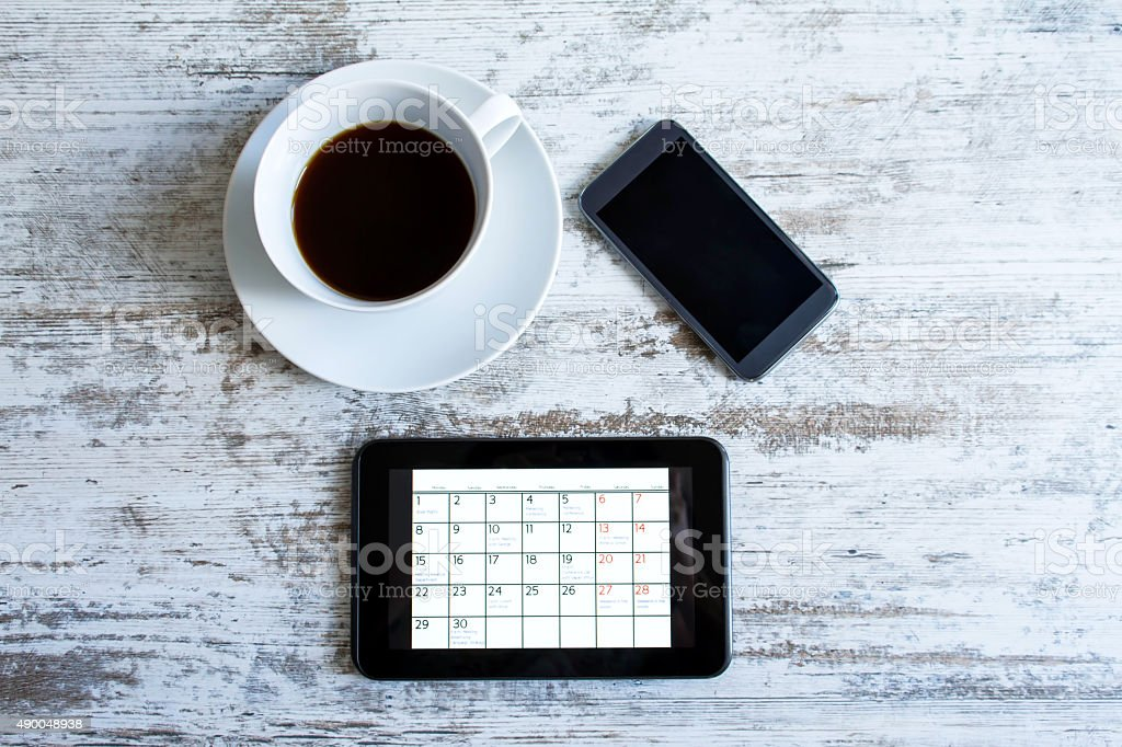 Checking monthly activities in the calendar in the tablet stock photo